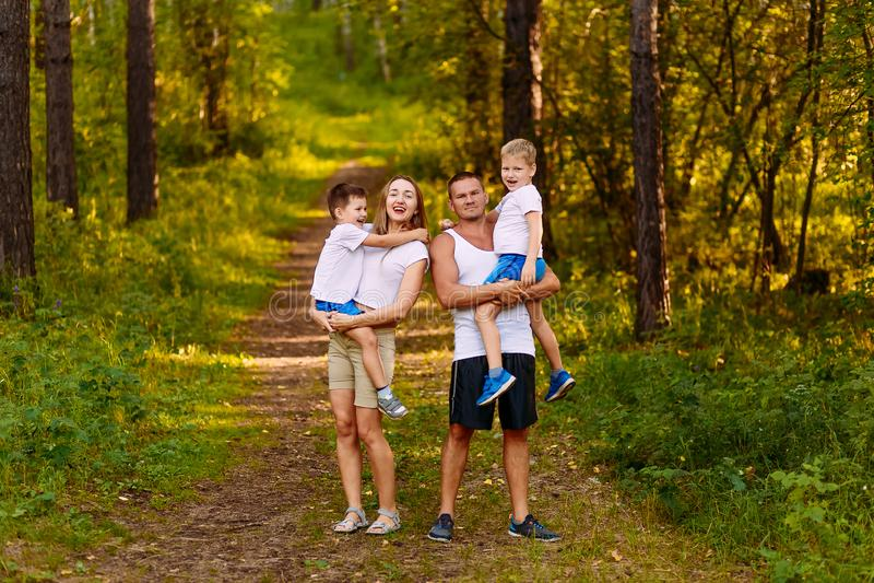 Os pais novos alegres guardam duas crianças em seus braços no ar livre do verão Fam?lia fotos de stock royalty free