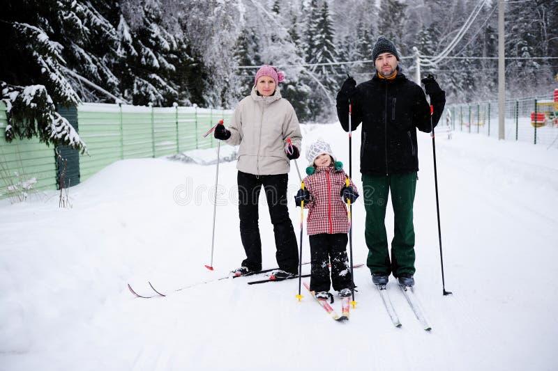 Os pais novos e sua filha fazem o esqui nórdico foto de stock royalty free