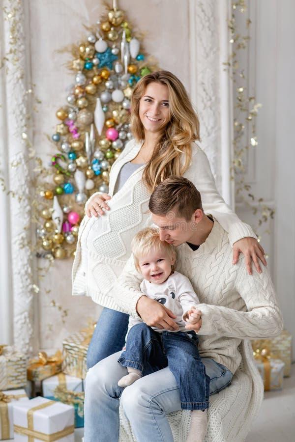 Os pais novos enganam ao redor e jogam com pouco filho Família feliz que tem o divertimento em casa Manhã de Natal na vida brilha imagem de stock royalty free