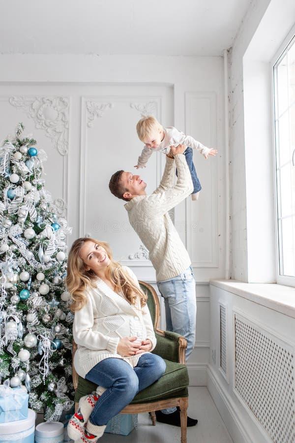 Os pais novos enganam ao redor e jogam com pouco filho Família feliz que tem o divertimento em casa Manhã de Natal na vida brilha fotos de stock royalty free