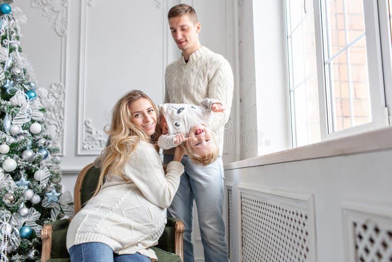 Os pais novos enganam ao redor e jogam com pouco filho Família feliz que tem o divertimento em casa Manhã de Natal na vida brilha imagens de stock royalty free