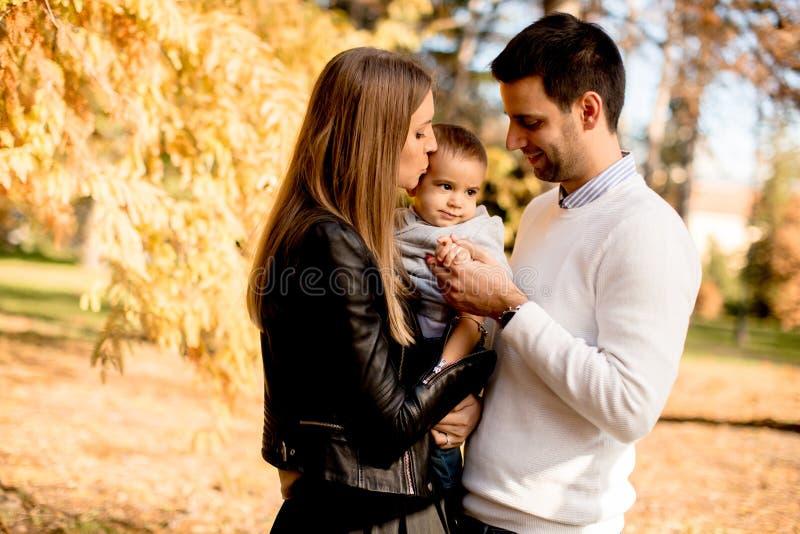 Os pais novos felizes com o bebê no outono estacionam fotos de stock royalty free