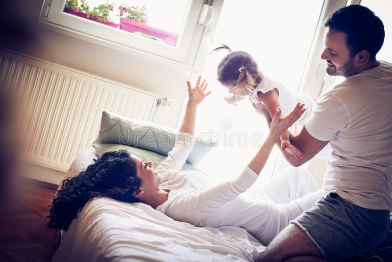 Os pais novos felizes com sua menina têm o jogo fotografia de stock royalty free