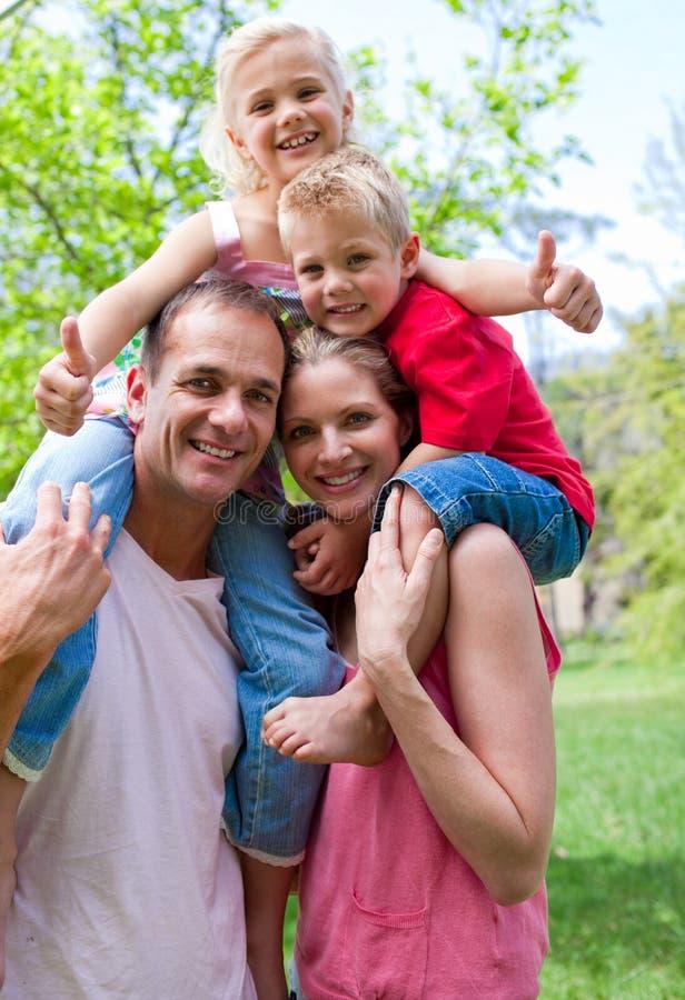 Os pais que dão suas crianças andam às cavalitas o passeio fotografia de stock