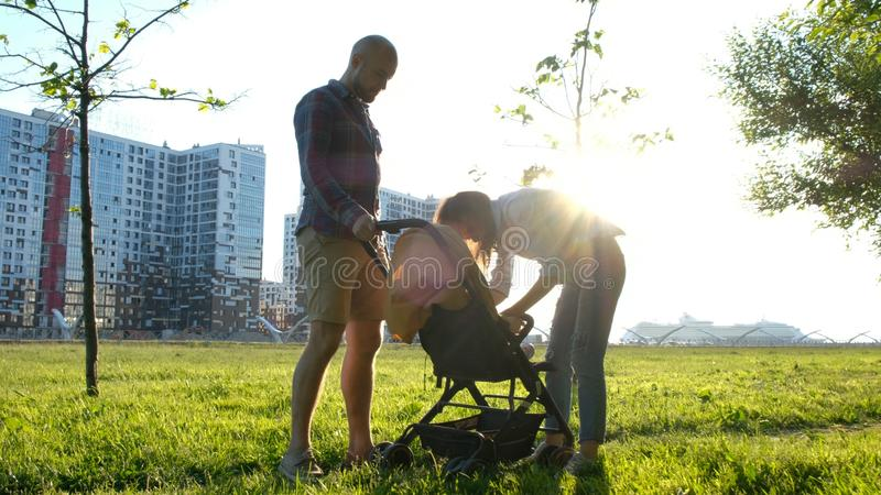 Os pais sentam para baixo o bebê no carrinho de criança Família nova feliz que tem um resto na natureza em um parque no por do so foto de stock royalty free