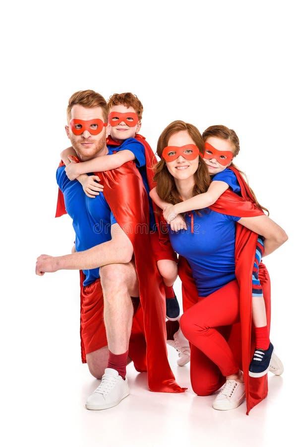 os pais super felizes que rebocam o sorriso adorável caçoam nas máscaras e nos casacos foto de stock royalty free