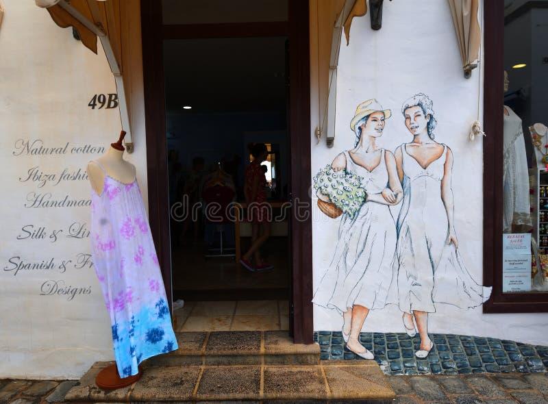 Os panos das senhoras compram parte dianteira com figuras pintadas das mulheres na parede fotografia de stock