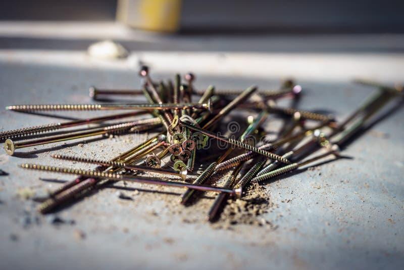 Os parafusos de madeira longos encontram-se dispersado no assoalho no canteiro de obras foto de stock
