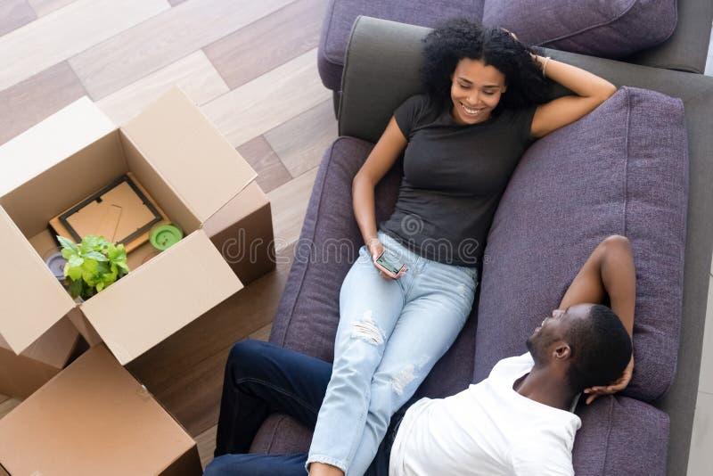 Os pares afro-americanos entusiasmados da vista superior que tomam a ruptura, desembalam caixas fotos de stock royalty free