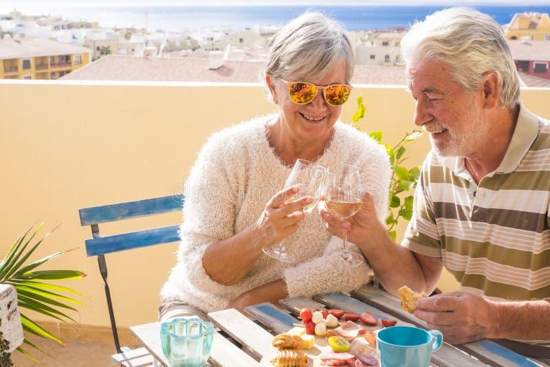 Os pares agradáveis de adulto aposentado ficam junto no pterrace do roofto que come e que bebe alguns alimento e bebida povos fel fotografia de stock royalty free