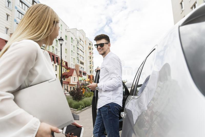 Os pares agradáveis estão estando junto exteriores na rua O indivíduo está inclinando-se na porta de carro Veste vidros A menina  fotos de stock