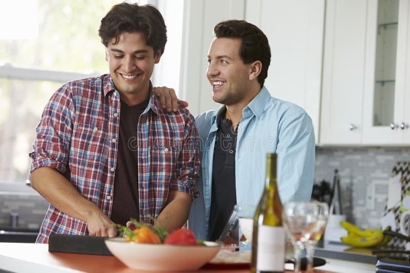 Os pares alegres masculinos que preparam uma refeição consultam uma tabuleta digital imagem de stock royalty free