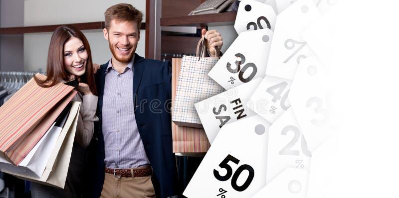Os pares alegres mostram suas compras após a compra imagens de stock royalty free