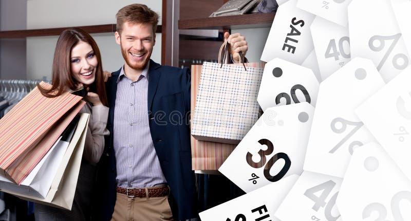 Os pares alegres mostram suas compras após a venda fotografia de stock