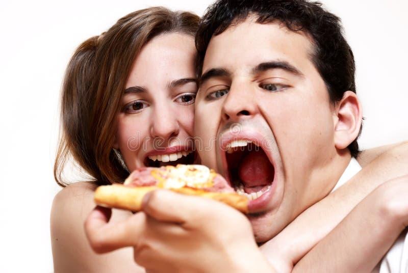 Os pares alegres que comem uma pizza imagem de stock
