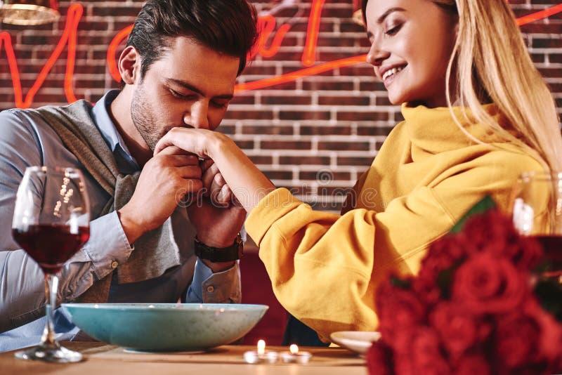 Os pares amam a história - o homem considerável beija a mão da jovem mulher com paixão fotos de stock royalty free