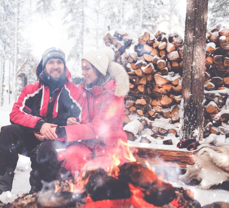 Os pares aproximam a fogueira na paisagem do inverno imagem de stock royalty free