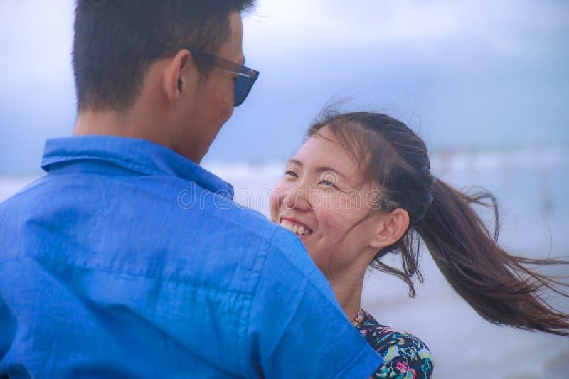 Os pares asiáticos chineses felizes e bonitos novos com mulher abraçam seu noivo romântico e afagam na praia fotografia de stock