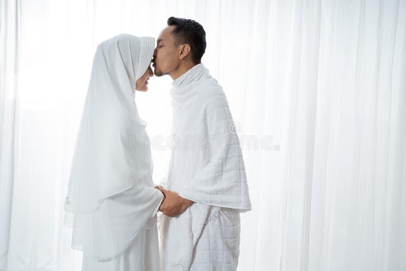 Os pares asiáticos muçulmanos agitam as mãos e o marido que beijam sua esposa fotografia de stock