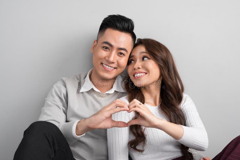 Os pares asiáticos novos fazem o símbolo do coração de suas mãos fotos de stock royalty free