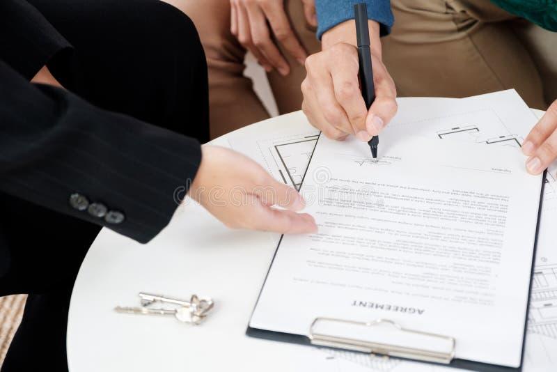 Os pares asiáticos que compram o contrato do sinal da casa nova com o corretor de imóveis na casa nova, fecham-se acima da mão do imagens de stock royalty free