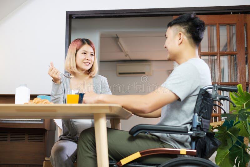 Os pares asiáticos tomam o café da manhã em casa a esposa que guarda a mão e incentiva o marido deficiente que senta-se na cadeir foto de stock royalty free