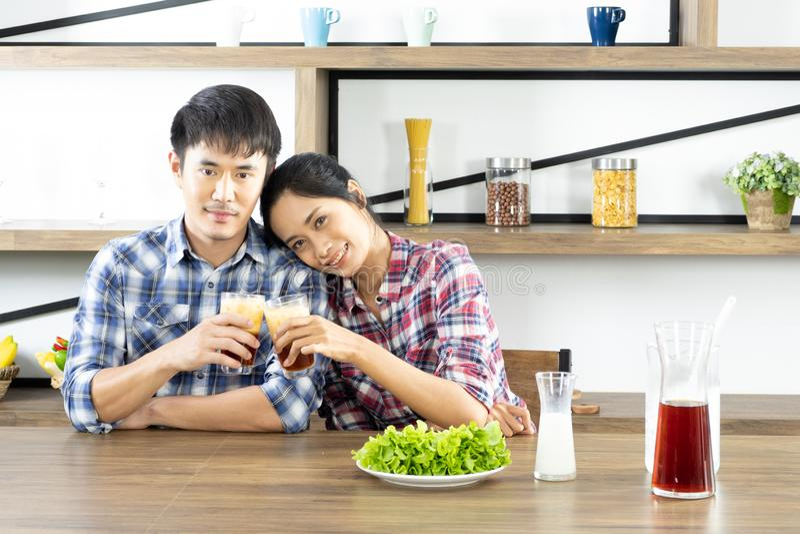 Os pares asi?ticos novos est?o felizes cozinhar junto, duas fam?lias est?o ajudando-se a preparar-se para cozinhar na cozinha imagens de stock