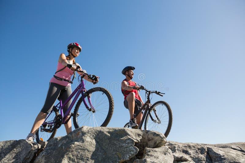 Os pares ativos em uma bicicleta montam no campo imagens de stock