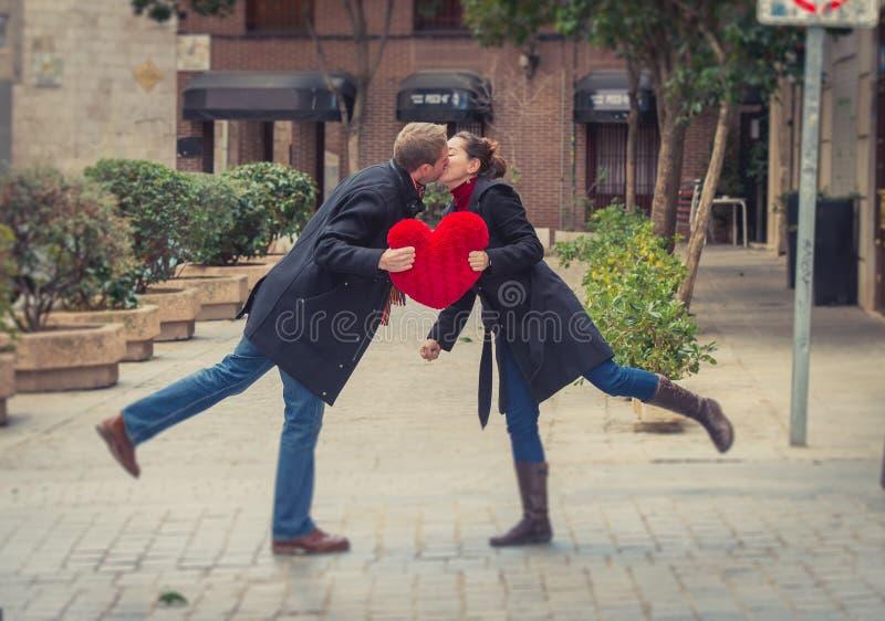 Os pares atrativos que beijam com um coração vermelho descansam fotos de stock