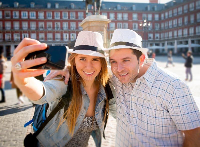 Os pares bonitos do turista dos amigos que visitam Europa em estudantes dos feriados trocam a tomada da imagem do selfie imagem de stock