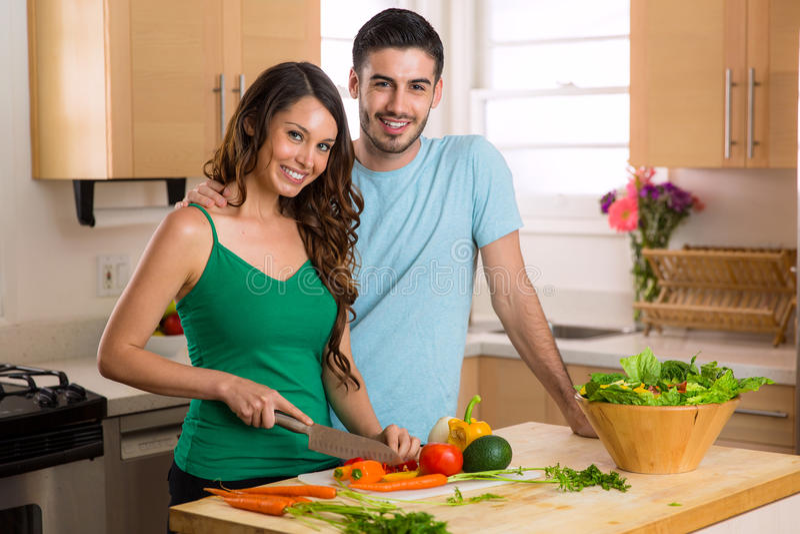 Os pares bonitos dos cozinheiros chefe home preparam nutrição saudável feliz um ponto baixo baseado - refeição da caloria imagem de stock royalty free