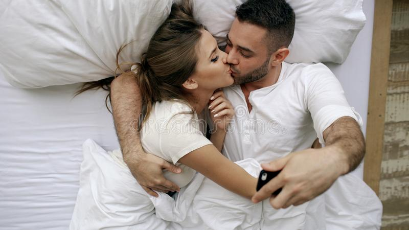 Os pares bonitos e loving novos tomam a imagem do selfie na câmera do smartphone e beijam-na ao encontrar-se na cama na manhã fotos de stock