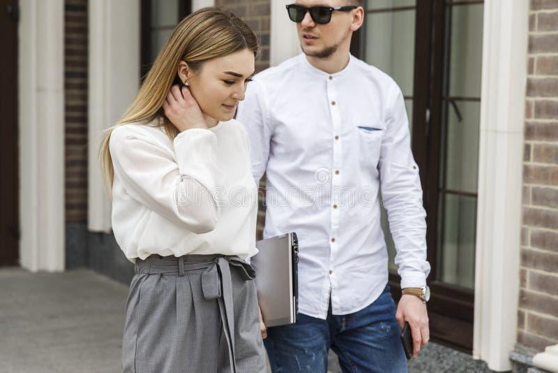 Os pares bonitos estão andando junto na rua O indivíduo olha para trás Veste vidros Menina que olha para baixo imagens de stock