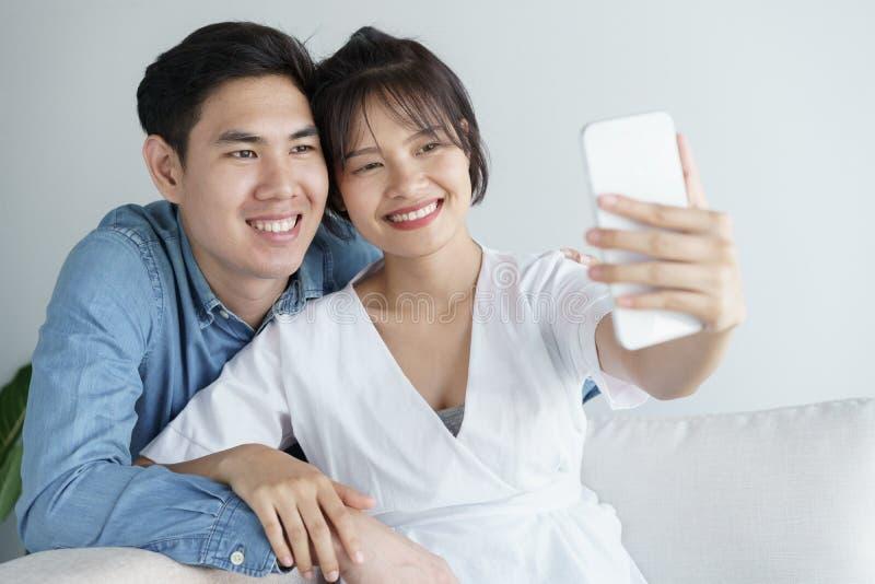 Os pares bonitos no amor são de aperto e de assento no sofá São selfie na manhã dentro em casa, vestindo equipamentos ocasionais fotos de stock