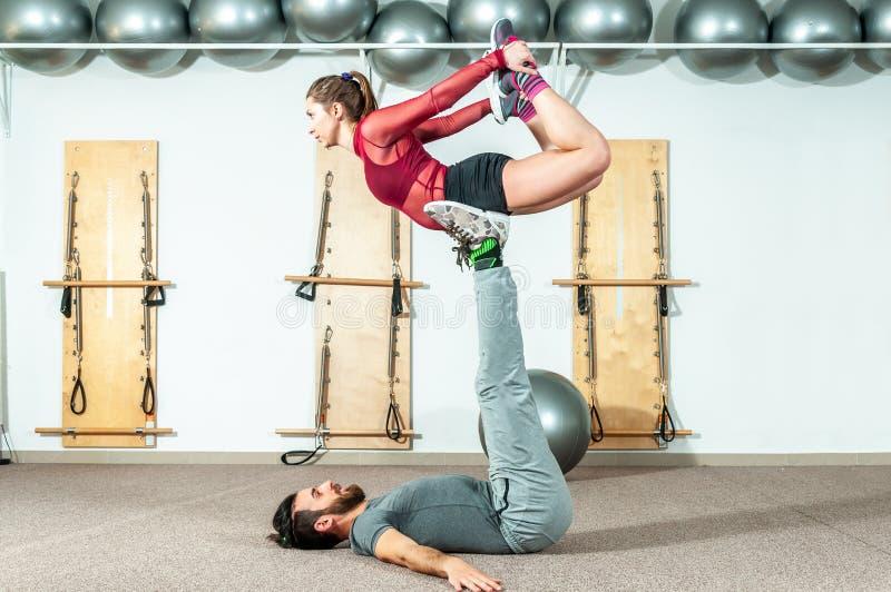 Os pares bonitos novos da aptidão malham o exercício acrobático extremo como a preparação para a competição, pessoa real do foco  imagens de stock