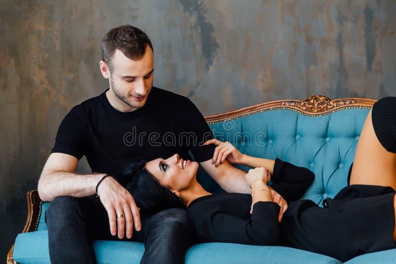 Os pares bonitos novos na roupa escura em um vintage de turquesa deitam imagem de stock