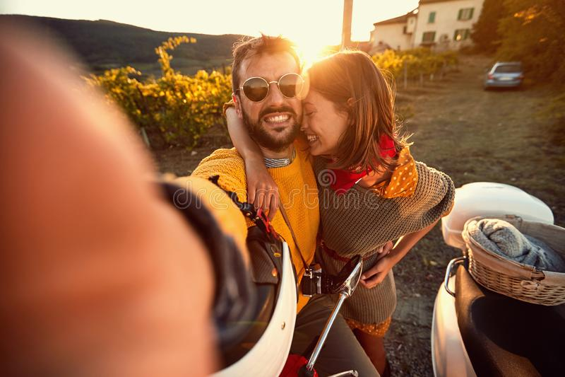 Os pares bonitos tomam o selfie usando um telefone esperto e sorrindo ao sentar-se em um 'trotinette' imagens de stock