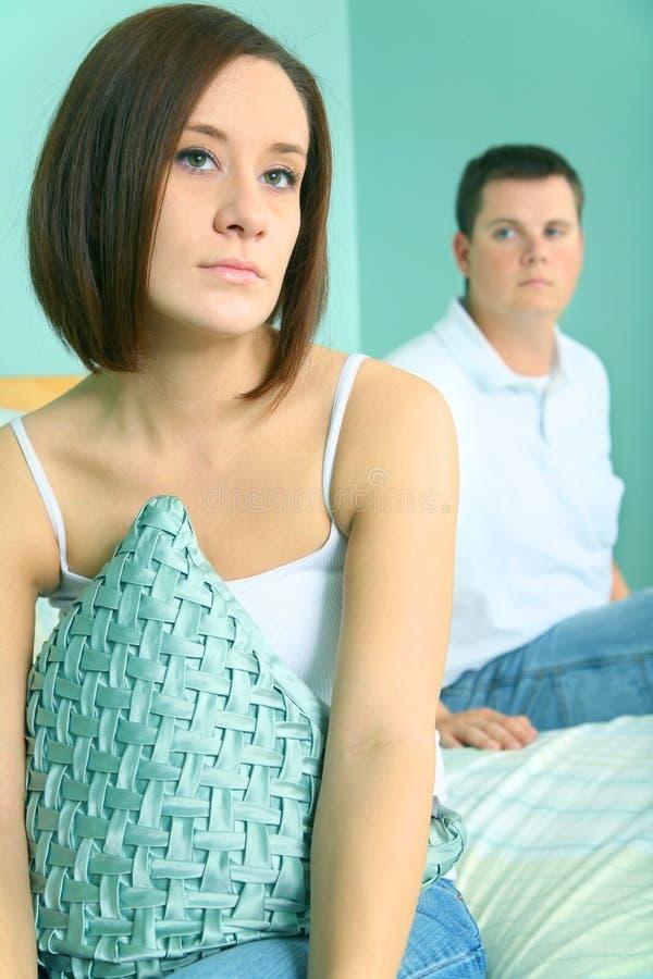 Os pares caucasianos novos deprimidos sentam-se no lado da cama fotos de stock