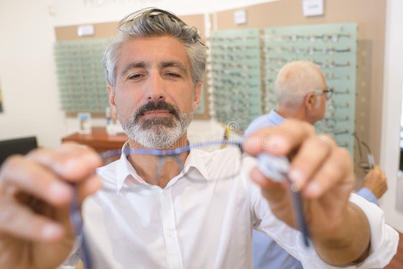 Os pares cedendo do oftalmologista considerável eye vidros ao paciente fotos de stock