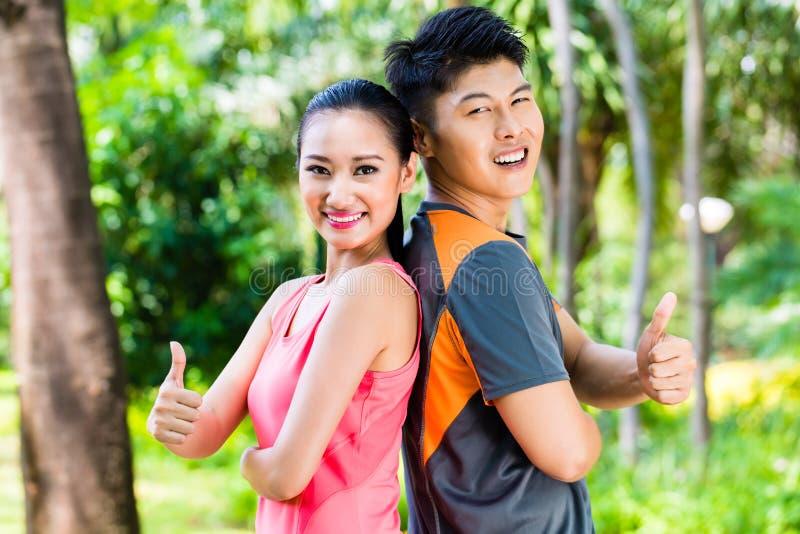 Os pares chineses asiáticos terminam correr o treinamento no parque imagem de stock royalty free