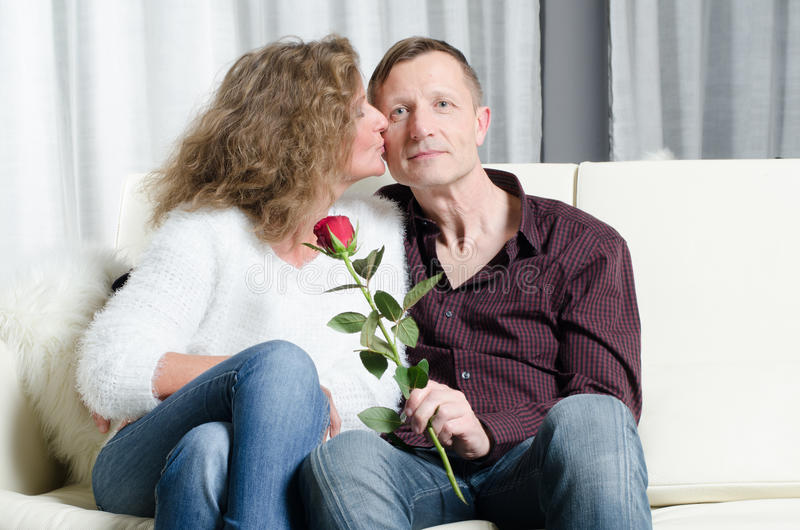Os pares com aumentaram beijando no sofá fotografia de stock royalty free