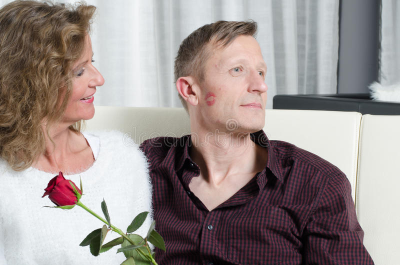 Os pares com aumentaram beijando no sofá foto de stock royalty free
