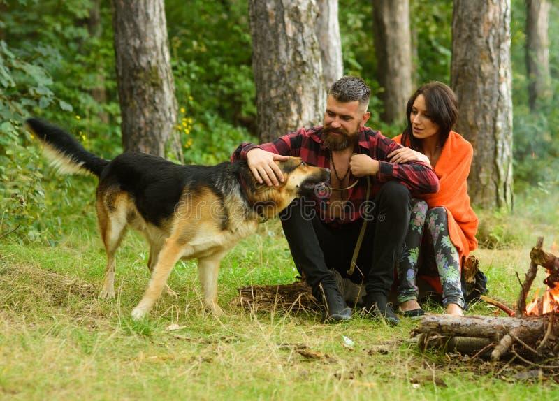 Os pares com cão-pastor alemão sentam-se perto da fogueira, fundo da floresta imagens de stock royalty free