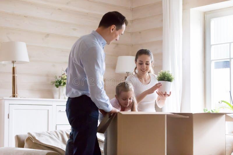 Os pares com filha desembalam seus pertences para mover-se na casa nova fotografia de stock