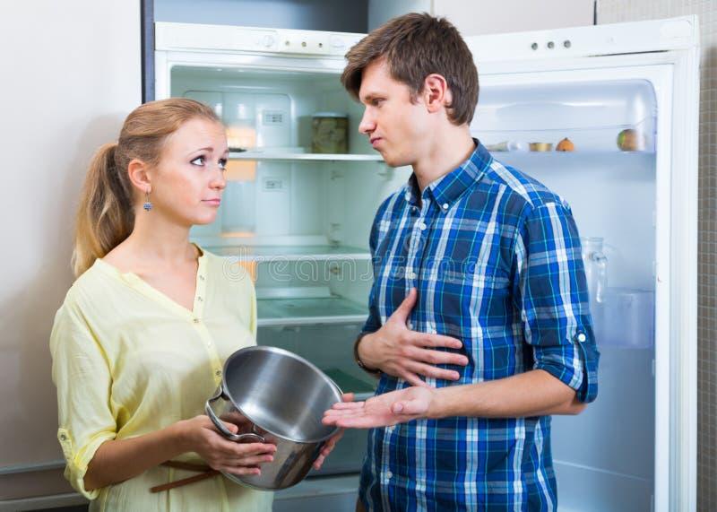 Os pares com fome aproximam o refrigerador vazio fotografia de stock royalty free