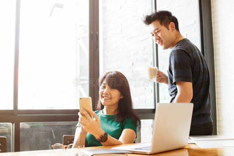 Os pares da união feliz que leem a mensagem entrante dos sms no smartphone conectaram ao wifi livre ao beber o café na manhã Sele fotos de stock royalty free