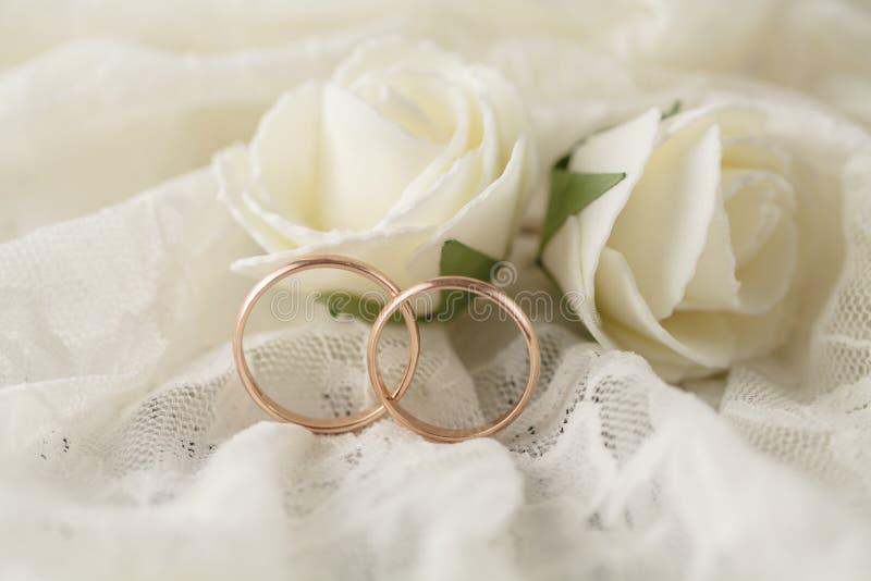 Os pares de alianças de casamento douradas sobre o convite cardam decorado com laço fotos de stock