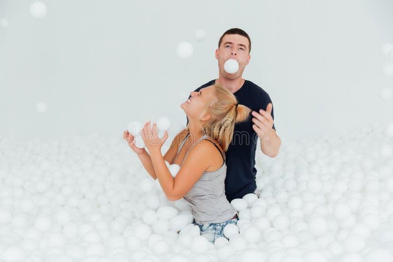 Os pares de amigos loving têm o divertimento cercados pelas bolas plásticas brancas em uma piscina seca imagens de stock royalty free