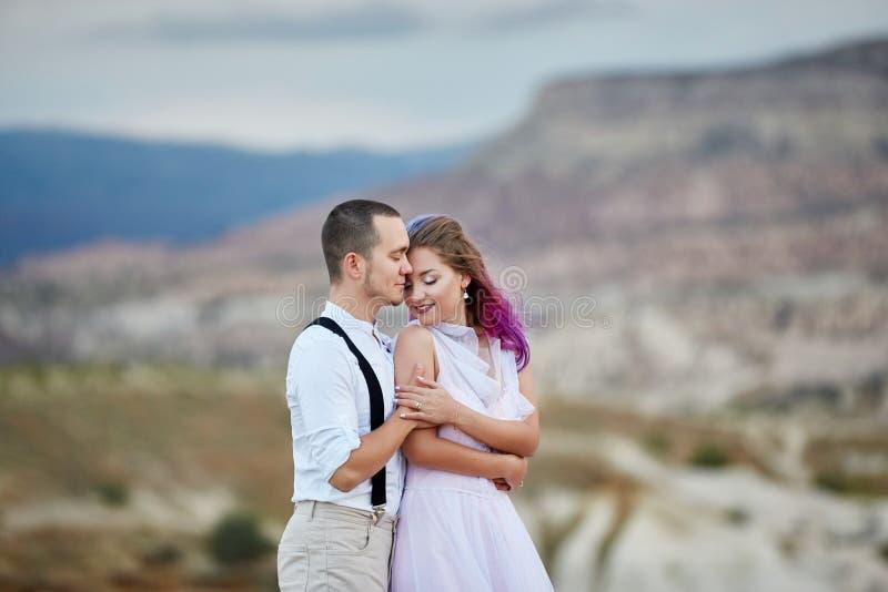 Os pares de amor do dia de Valentim em abraços e beijos da natureza, homem e mulher amam-se Montanhas do cappadocia no peru foto de stock royalty free