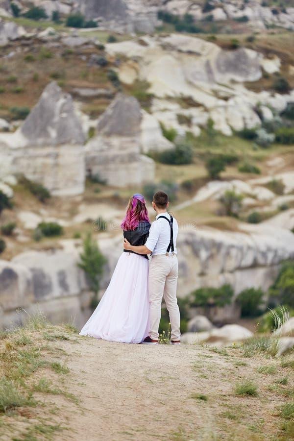 Os pares de amor do dia de Valentim em abraços e beijos da natureza, homem e mulher amam-se Montanhas do cappadocia no peru fotografia de stock royalty free